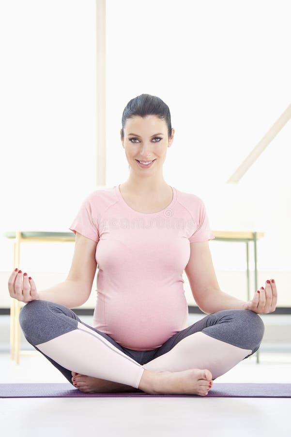 Femme enceinte dans la pose de yoga photographie stock