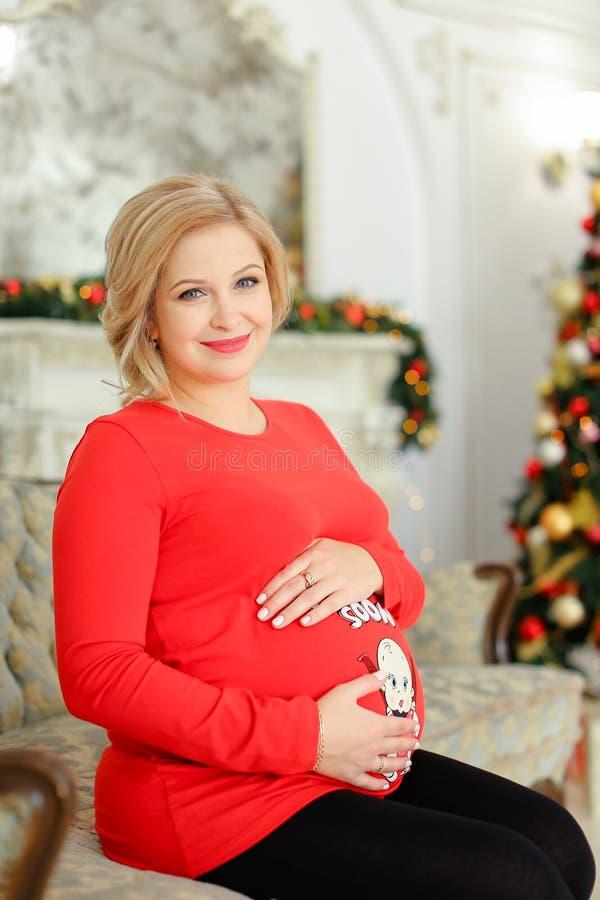 Femme enceinte de Caucasain utilisant le chandail rouge étreignant bely et se reposant sur le sofa près de l'arbre de Noël images libres de droits
