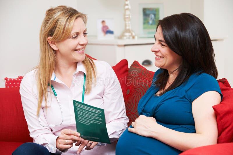 Femme enceinte de Discussing Literature With de sage-femme pendant la maison Vi images libres de droits