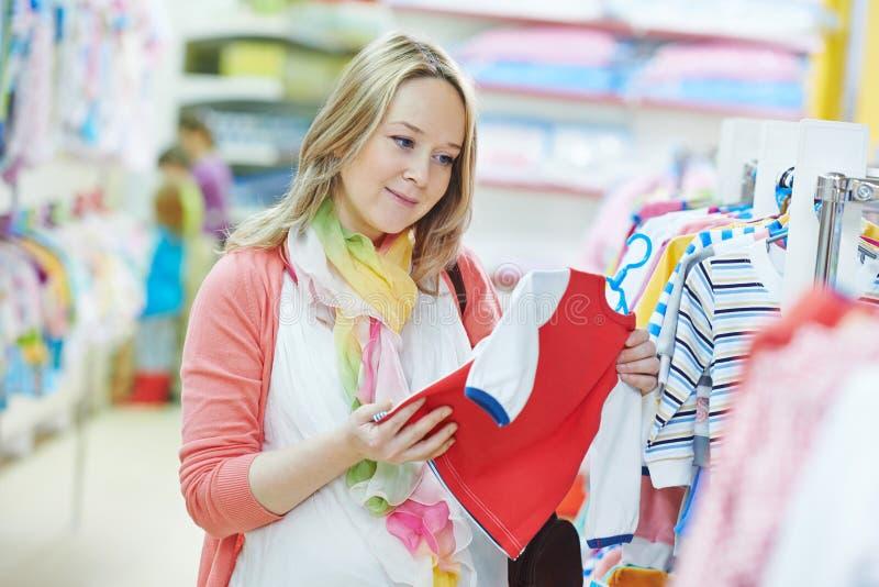 Femme enceinte de jeunes à la boutique de vêtements image stock