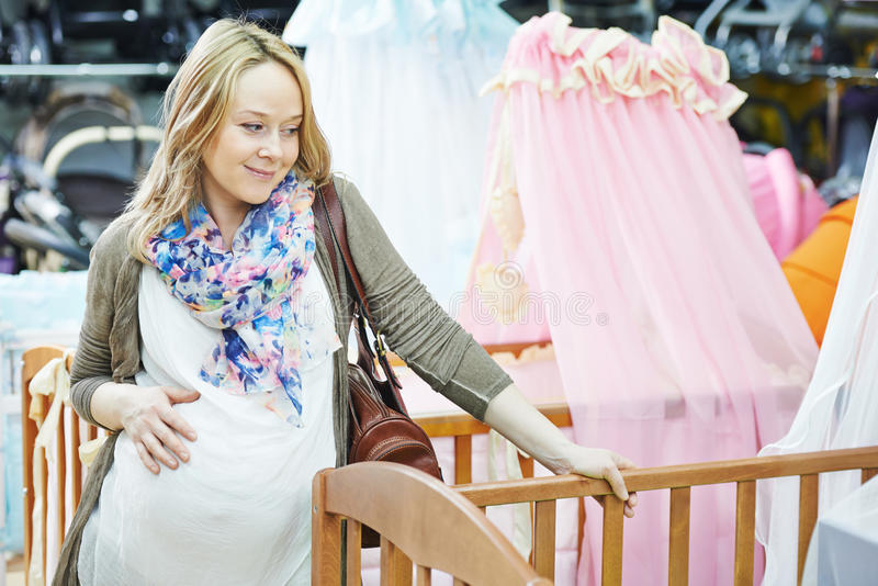 Femme enceinte de jeunes choisissant le berceau photos libres de droits
