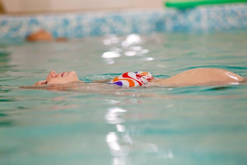 Femme enceinte de jeunes dans la piscine images libres de droits