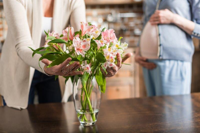 femme enceinte de jeunes et sa mère supérieure avec le bouquet des fleurs images stock