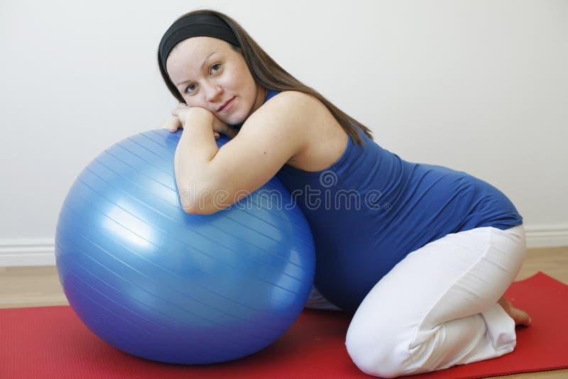 Femme enceinte de jeunes faisant un exercice W de relaxation image libre de droits