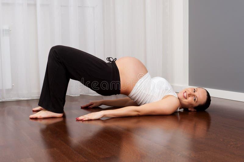 Femme enceinte de smiley faisant l'exercice à la maison photographie stock