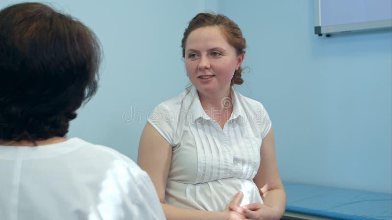 Femme enceinte de sourire avec son docteur dans la chambre d'hôpital photo stock