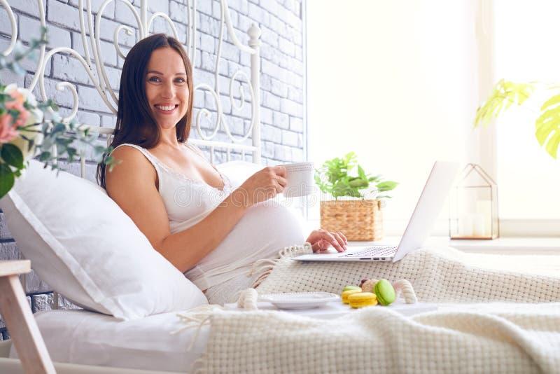 Femme enceinte de sourire déjeunant dans le lit avec l'ordinateur portable photos libres de droits