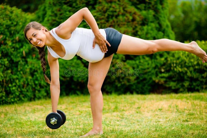 Femme enceinte de sourire faisant l'haltère simple Deadlift de jambe dans le pair image libre de droits