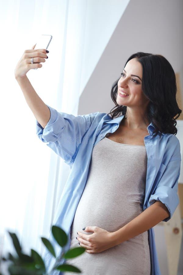 Femme enceinte de sourire prenant un autoportrait avec son smartphone tenant la fenêtre proche photo stock