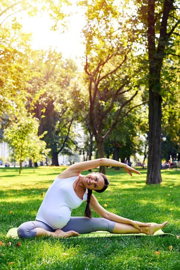 Femme enceinte de sourire s'étirant sur le tapis de yoga en parc photo stock