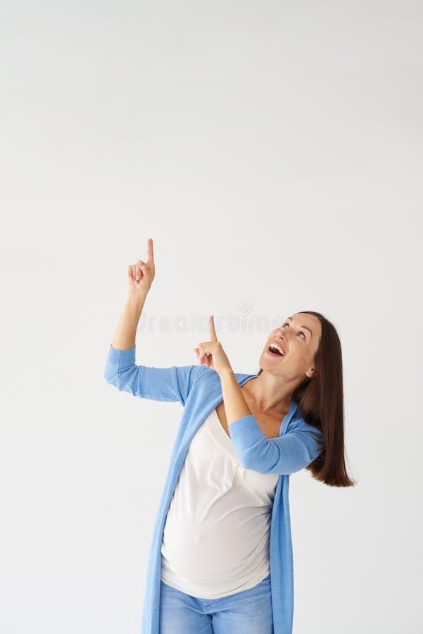 Femme enceinte de sourire se dirigeant vers le haut avec des doigts photos libres de droits