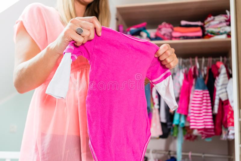 Femme enceinte devant la garde-robe dans la chambre de childs photographie stock
