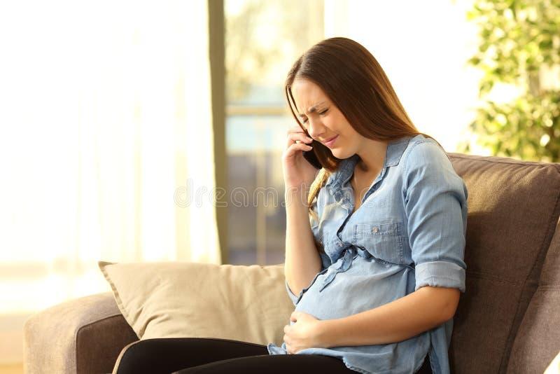 Femme enceinte douloureuse appelle l'aide médicale image stock