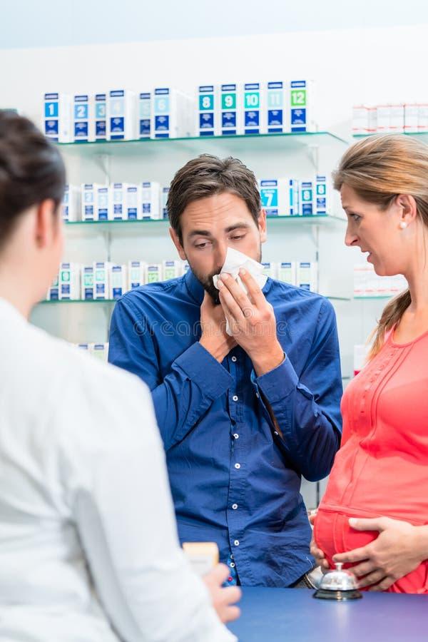 Femme enceinte et homme avec la grippe dans la pharmacie photos libres de droits