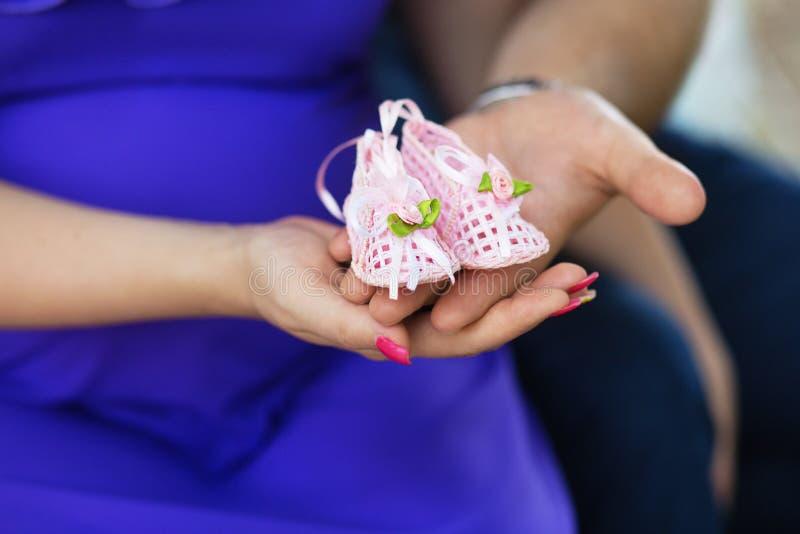Femme enceinte et son mari tenant des chaussures de bébé sur ses mains image libre de droits