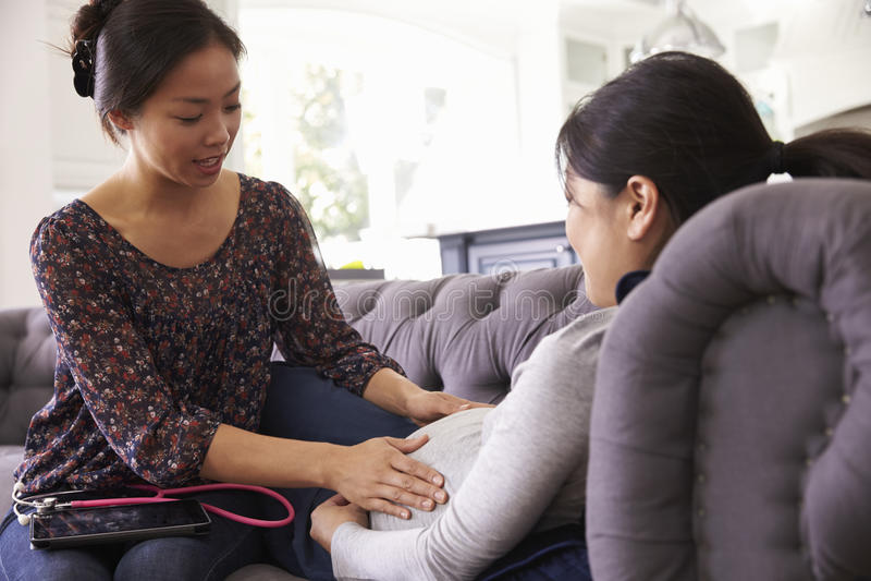 Femme enceinte examiné à la maison par la sage-femme photos stock
