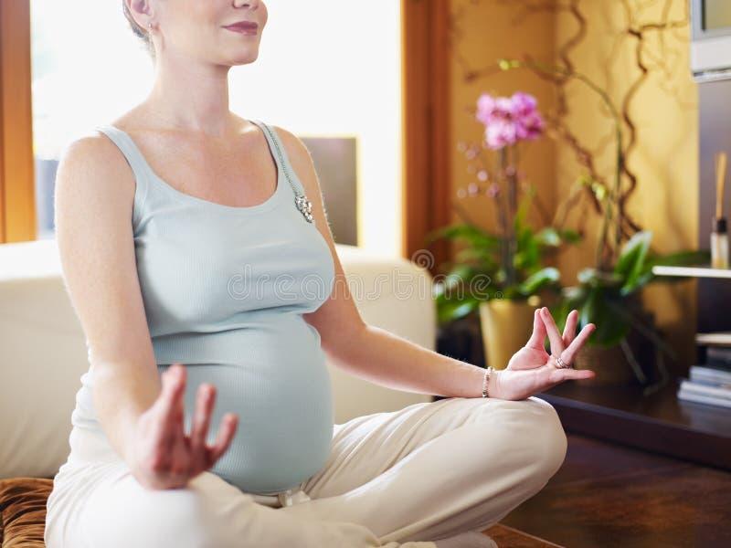 Femme enceinte faisant le yoga à la maison image stock