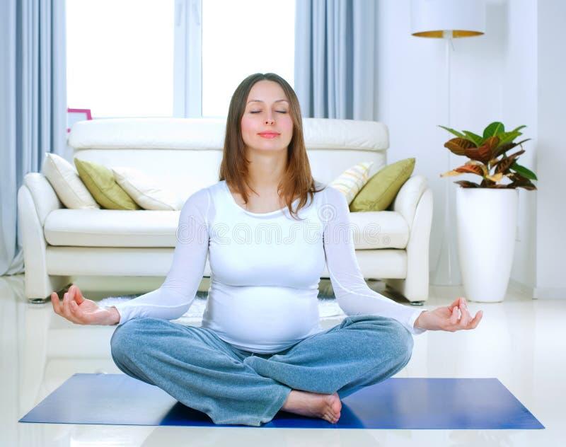 Femme enceinte faisant le yoga photographie stock libre de droits