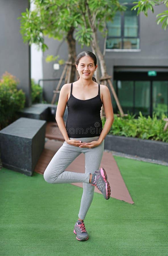 Femme enceinte faisant le yoga dehors images stock