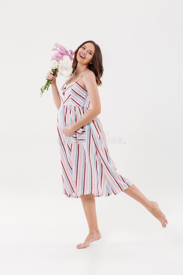 Femme enceinte gaie tenant des fleurs images libres de droits