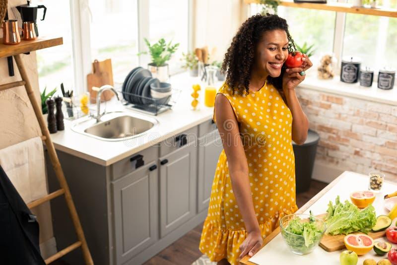 Femme enceinte gaie touchant la tomate avec une joue image libre de droits