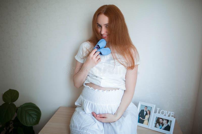 Femme enceinte heureuse à la maison tenant des chaussettes bleues pour le bébé image stock