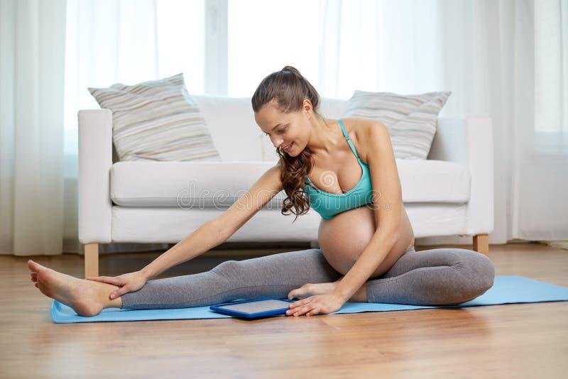 Femme enceinte heureuse avec l'exercice de PC de comprimé images libres de droits