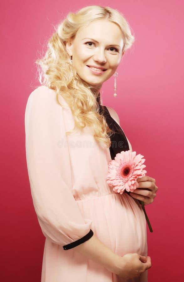 Femme enceinte heureuse avec le gerber photographie stock