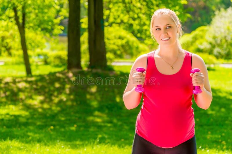 Femme enceinte heureuse observant son chiffre faire des exercices photo libre de droits