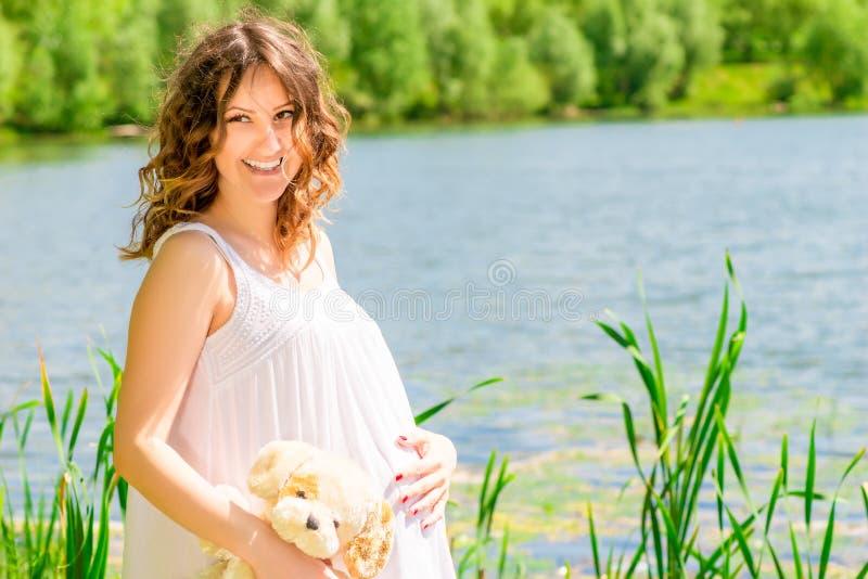 Femme enceinte heureuse posant sur la nature image libre de droits
