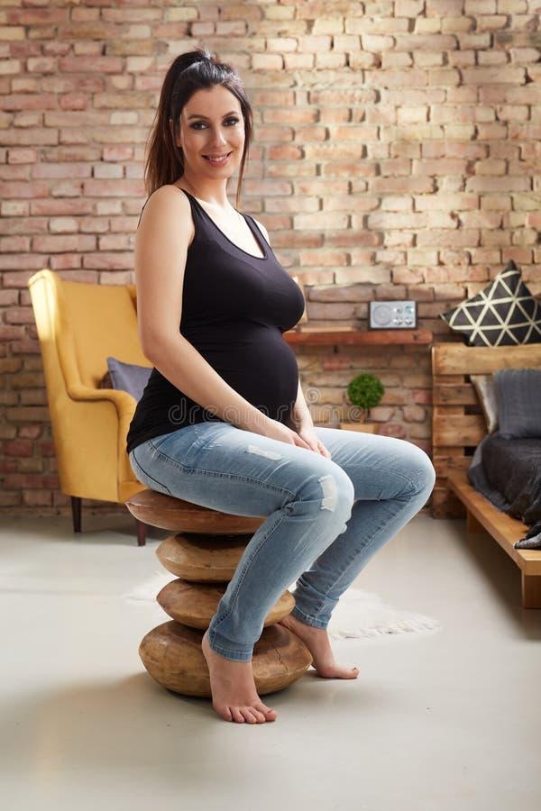 Femme enceinte heureuse s'asseyant à la maison images stock