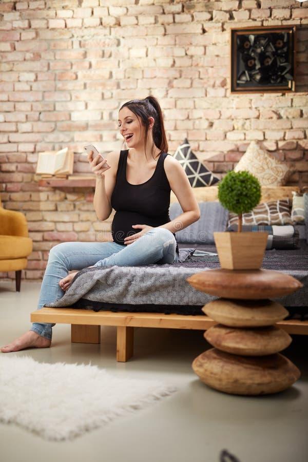 Femme enceinte heureuse s'asseyant à la maison photos libres de droits