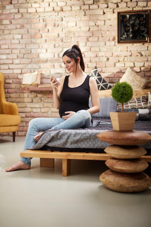 Femme enceinte heureuse s'asseyant à la maison photographie stock libre de droits