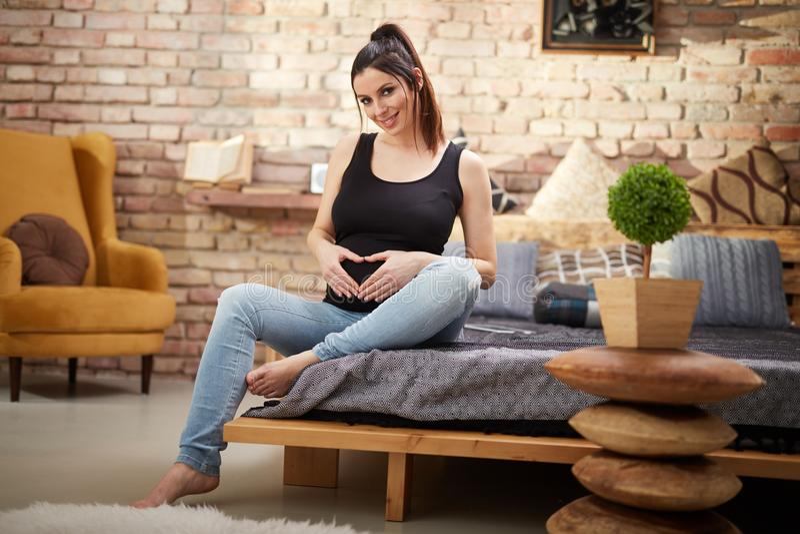Femme enceinte heureuse s'asseyant sur le lit à la maison photo libre de droits