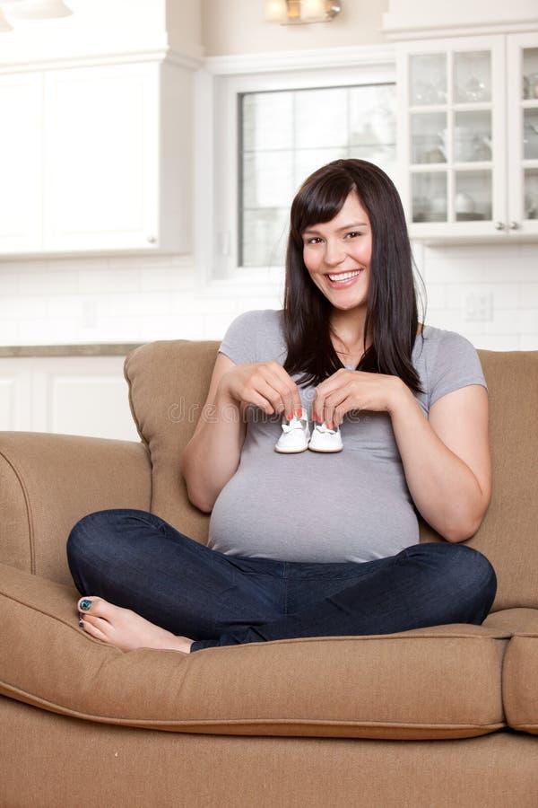Femme enceinte heureuse tenant des chaussures de bébé photo libre de droits