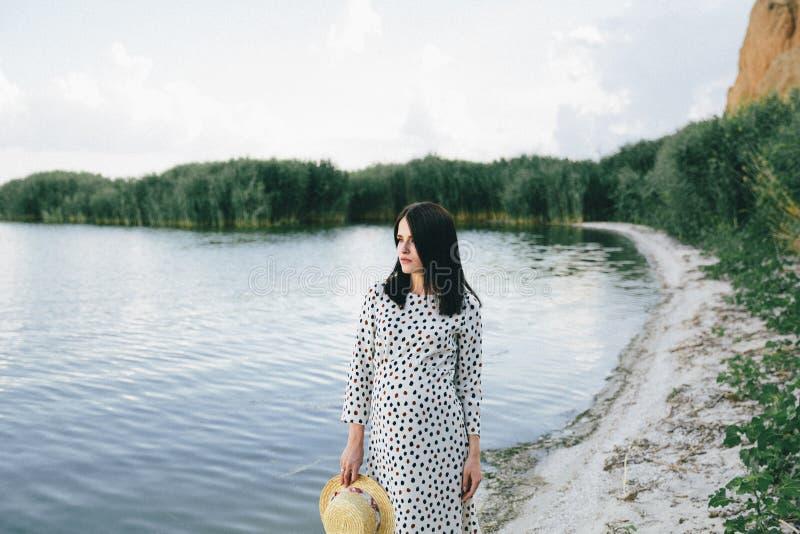 Femme enceinte la position de robe de point de polka sur le fond de rivière et en touchant son ventre images libres de droits