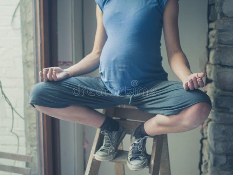 Femme enceinte méditant sur l'échelle photo stock