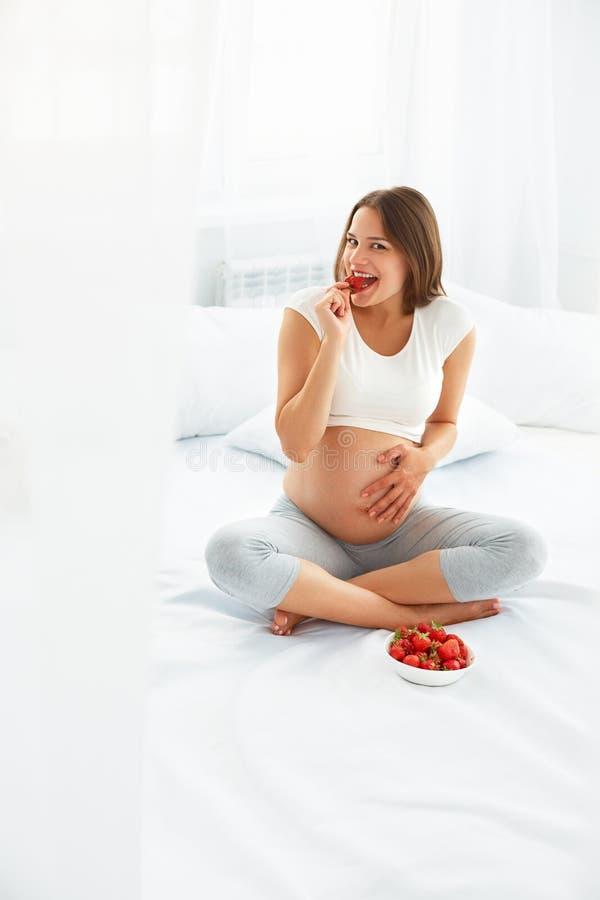 Femme enceinte mangeant la fraise à la maison Concept sain de nourriture images libres de droits