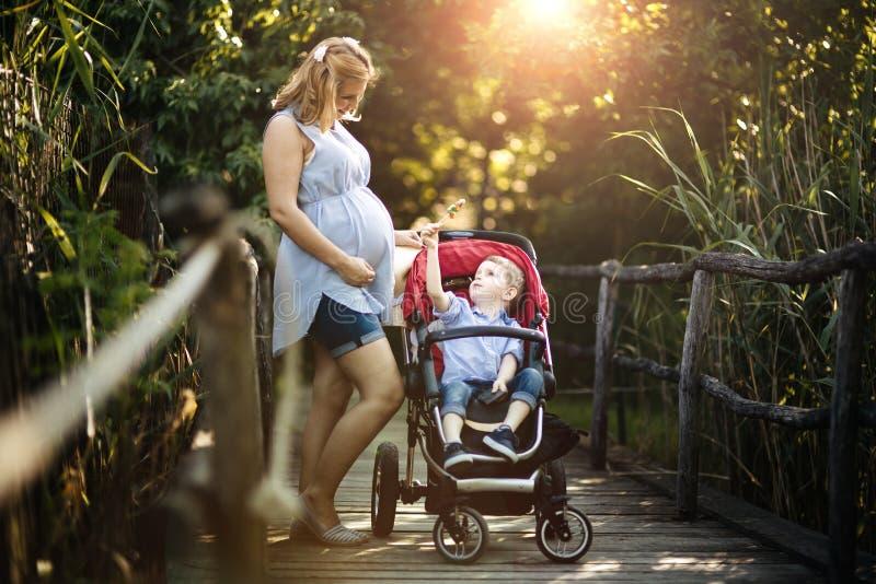 Femme enceinte marchant avec l'enfant en nature images stock