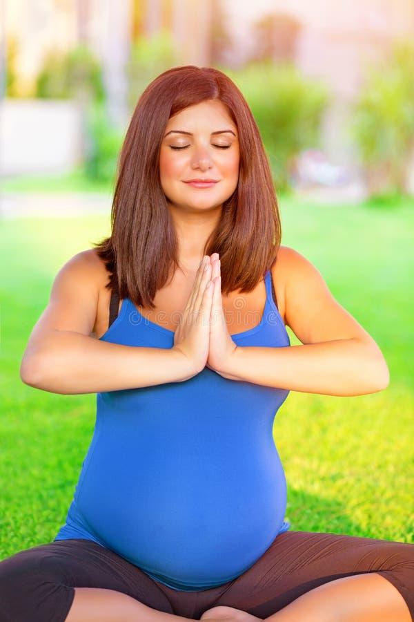 Femme enceinte occupée dans le yoga dehors photo stock