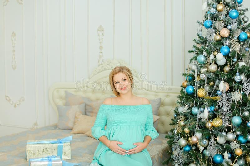 Femme enceinte portant la robe bleue étreignant le ventre et se reposant près de l'arbre et des présents de Noël images libres de droits