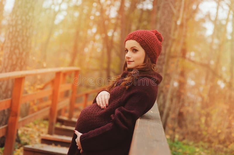 Femme enceinte réfléchie dans l'équipement confortable doucement chaud de marsala marchant dehors photo libre de droits