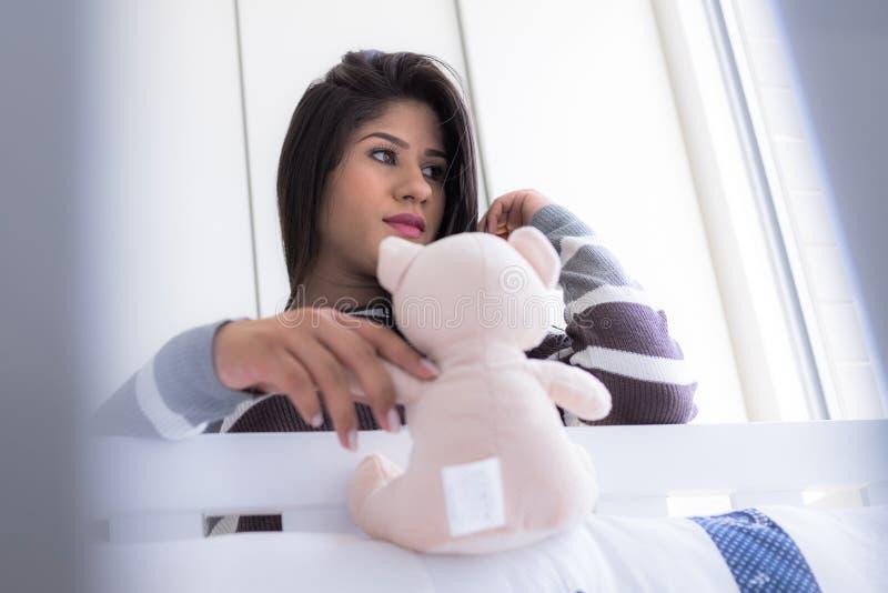 Femme enceinte regardant la huche du ` s de bébé photo stock