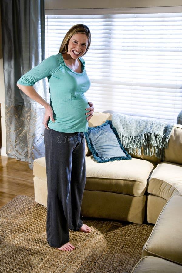 Femme enceinte restant dans la salle de séjour photo stock