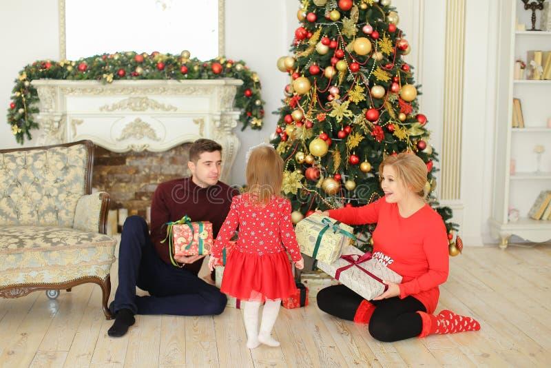 Femme enceinte s'asseyant avec l'homme et la petite fille près de l'arbre de Noël et des présents gifting photographie stock