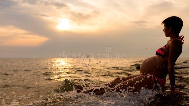 Femme enceinte s'asseyant dans l'eau peu profonde image libre de droits