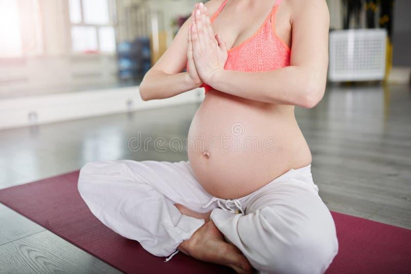 Femme enceinte s'asseyant dans la pose de lotus pliant ses mains images libres de droits