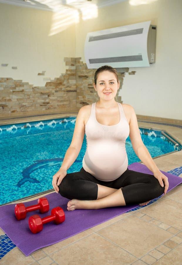 Femme enceinte s'asseyant en position de lotus sur le tapis de forme physique photos libres de droits