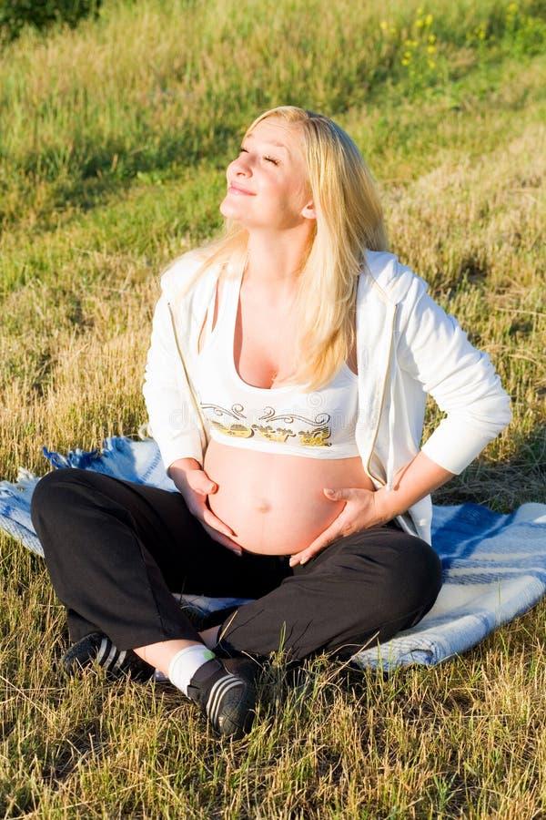 Femme enceinte s'asseyant sur l'herbe image libre de droits