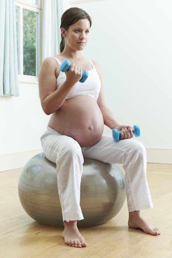 Femme enceinte s'asseyant sur la boule d'exercice avec des poids images stock